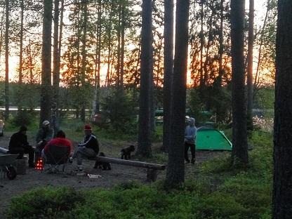 ryhmä nuotion äärellä telttaleirillä